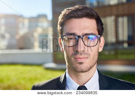 Young businessman in eyeglasses and formalwear looking at camera in urban environment