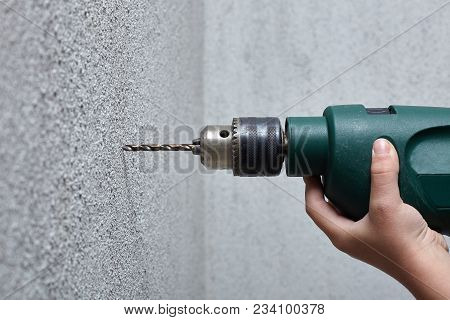 Worker Drilling A Hole Into The Wall With An Electric Drill.