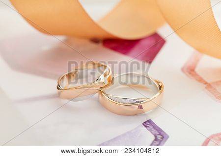 Two White And Rose Gold Wedding Rings On Pastel Background With Ribbons. Silver And Gold Rings. Wedd