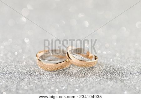 Wedding Rings On A Silver Sparkling Glitter Background With Bokeh. Shallow Focus. Copy Space