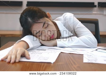 Tired Overworked Young Asian Business Woman Lying Down On The Desk In Office.