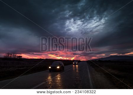 Straight Highway Road To A Dramatic Fiery Sunset Near Twilight With Cars Passing