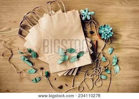Brown Craft Paper Bags Packaging Template With Stitch Sewing On Wooden Background. Packaging Templat