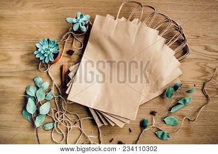 Brown Empty Kraft Paper Bags On Wooden Background. Packaging Template Mockup. Top View Package. Copy