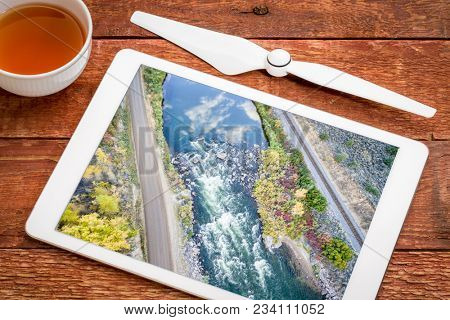 Rodeo Rapid on the upper Colorado River at Burns, Colorado, USA, - reviewing and editing aerial image on a digital tablet with a cup of tea