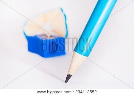 Blue Pencil With Blue Pencil Sharpener And Sharpening Shavings On White Background. Stationery. Offi