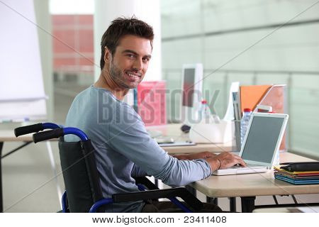 Man sitting at desk in wheelchair poster