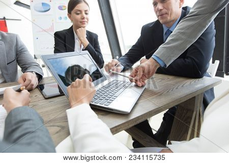 Business people in meeting room looking together at laptop screen