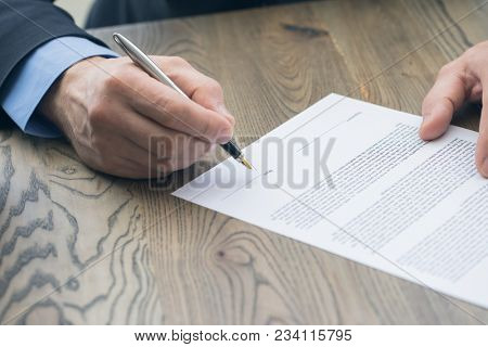 Businessman sitting at office desk signing a contract with shallow focus on date