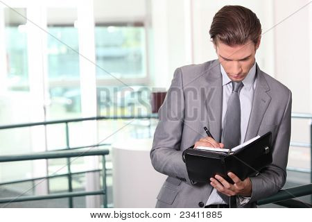 Businessman writing in diary