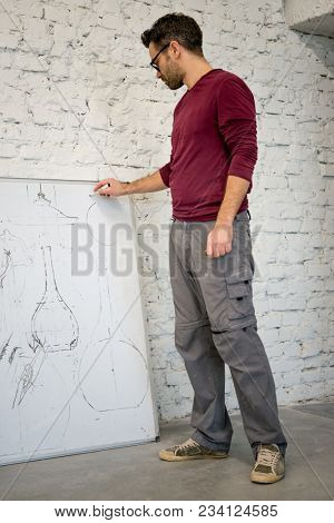 Young Designer Drawing the Sketch on the Big Whiteboard in the White Studio