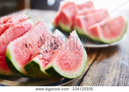 Sliced Slices Of Ripe Juicy Watermelon Lie On A Plate On A Wooden Table. Small Depth Of Field.