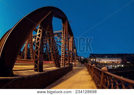 Vintage river bridge and industrial building at night