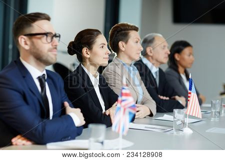 Group of international representatives in formalwear listening attentively report of one of speakers at political summit