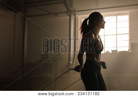 Young Woman Exercising Using Skipping Rope In Gym. Athletic Woman Training At The Gym.