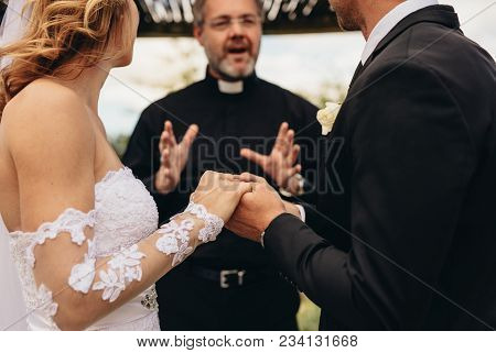 Bride And Groom Holding Hands In Presence Of Priest Reading Prayers During Wedding Ceremony. Close U