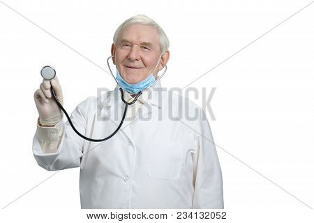 Old Smiling Doctor With Listen Your Heartbeat Using Stethoscope. Portrait Of Holding Stethoscope And