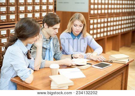 Group Of Serious Concentrated Student In Casual Clothing Reading Book Together Thoughtfully While Pr