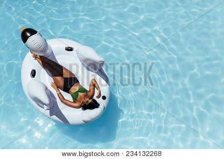 Overhead View Of Woman In Bikini Resting On An Inflatable Swan In Swimming Pool. Female Sunbathing O