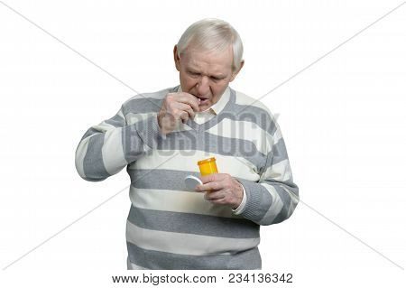 Old Man Taking Pill. Portrait Of Retired Man Swallowing Pills. White Isolated Background, Cutout.