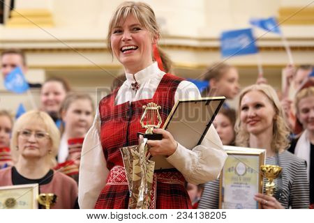 SAINT-PETERSBURG, RUSSIA - FEBRUARY 25, 2018: Representative of Children's Choir Lielvarde, Latvia with diploma of V Children and Youth World Choral Championship. First championship was held in 2011
