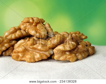 Walnuts On White Burlap On Green Natural Background. Beautiful Walnut Kernels With Free Copy Space.