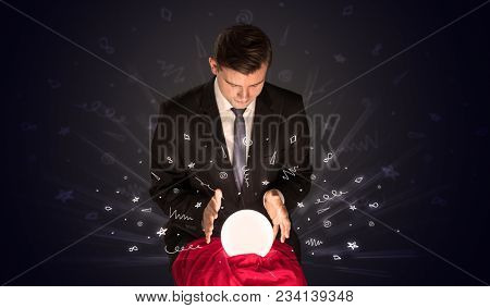 Gorgeous businessman looking to inspiration in a magic ball in his lap and doodle concept