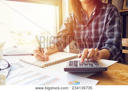 poster of Asian business woman using calculator for accounting and analyzing investment in front of computer laptop at office workspace.  banking , savings , accountant , finances and economy concept.