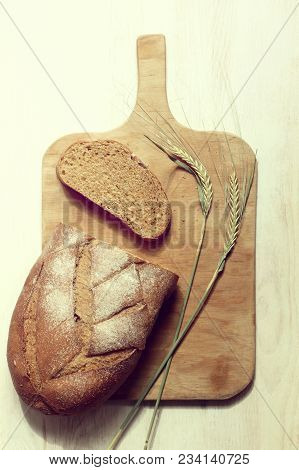 Slice Of Bread With A Slice And Spikelet On A Wooden Board Top View /appetizing Crust Of Fresh Baked