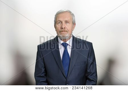 Confident Serious Old Businessman Portrait. Senior Caucasian Man In Suit In Blurred Background.