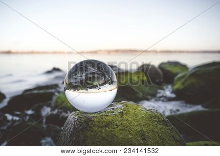 Crystal Ball On Moss Covered Rocks By The Sea In The Early Morning