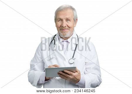 Portrait Of An Old Senior Smiling Doctor With Tablet. Physician With Stethoscope, White Isolated Bac