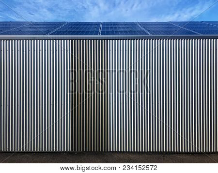 Modern Iron Warehouse Covered By Solar Panels Against Great Blue Sky