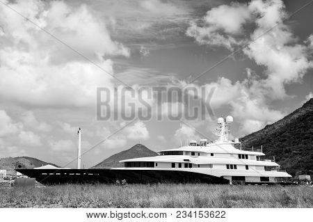 Yacht Boat Or Luxury Ship In Philipsburg, St Maarten On Mountain Landscape On Cloudy Blue Sky. Luxur