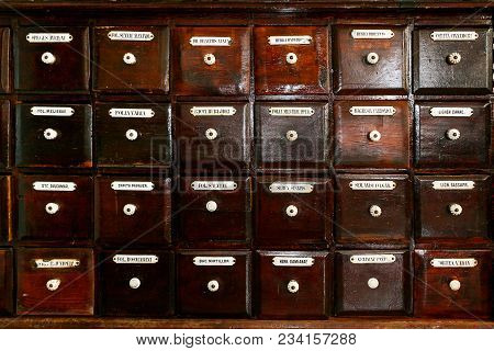 Retro Background Of Lot Of Old Wooden Dark Brown Apothecary Drawers With Labels.