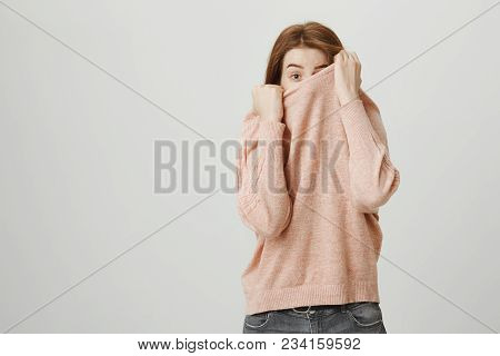 Studio Portrait Of Funny European Redhead Woman Hiding In Her Pullover While Peeking With One Eye An