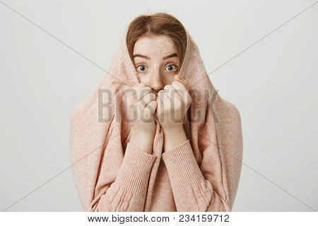 Indoor Shot Of Funny Cute Ginger Girl Hiding In Her Pullover And Peeking Through Collar, Holding Han