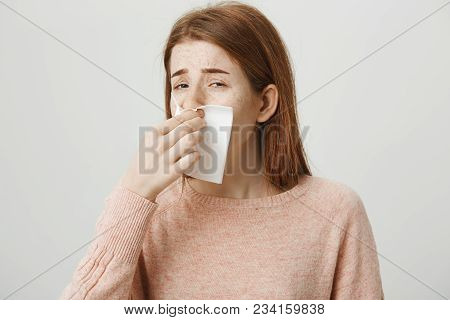 Close Up Portrait Of Sick Redhead European Student Sneezing And Wiping Nose With Napkin, Being Fed U