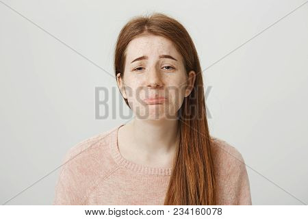 Close-up Portrait Of Sad Redhead Caucasian Girl With Gloomy Smile, Whining Or Crying With Frowned Ey