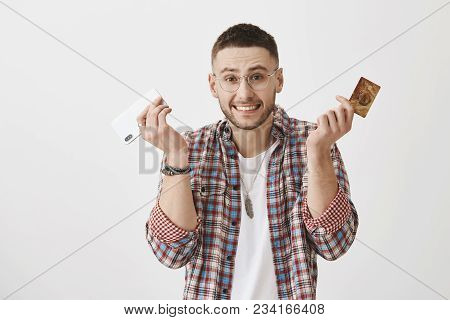 Sorry I Spent All Your Money. Clumsy Good-looking Male Shrugging And Holding Smartphone And Credit C