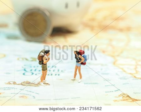 Miniature Traveler Saving Money In Piggy For Travel Backpack  On Wold Map For Travel Around The Worl