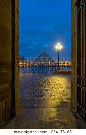 PARIS, FRANCE - DECEMBER 04, 2017: View of famous Louvre Museum with Louvre Pyramid at evening. Louvre Museum is one of the largest and most visited museums worldwide