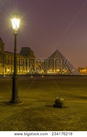 PARIS, FRANCE - DECEMBER 02, 2017: View of famous Louvre Museum with Louvre Pyramid at evening. Louvre Museum is one of the largest and most visited museums worldwide