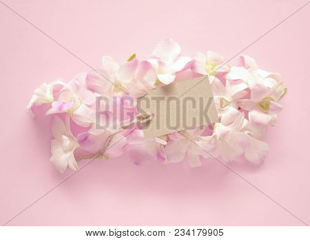Sweet Orchids Bouquet With A Blank Gift Tag For Valentines Or Anniversary Message On Pink Background