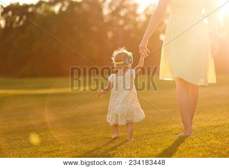 Mum With Little Girl They Go On Grass And Keep For Hand On The Sunset With Beams Glares