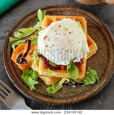 Homemade savory waffles with poached egg and salad