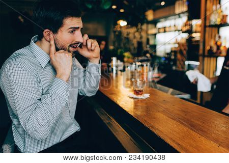 Dark-haired Guy Is Sitting At The Barman's Stand And Talking On The Phone. He Is Closing His Ear To