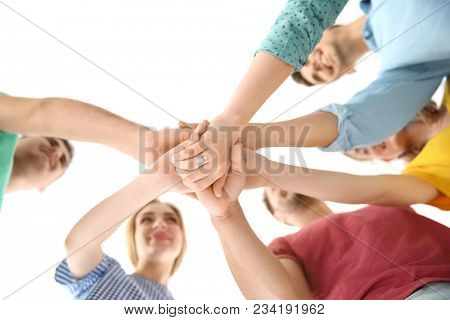 Young people putting hands together on light background. Unity concept