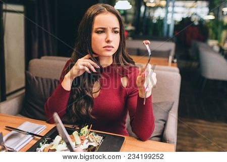 A Picture Of Beautiful Woman Sitting At The Table In Restaurant And Eating Her Salad. She Took A Pie