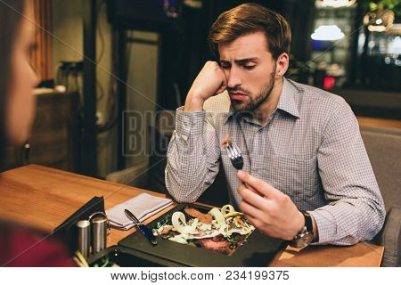 Pictue Of Guy Sitting Together With His Girlfriend And Eating Some Food They Have Ordered. Man Has F